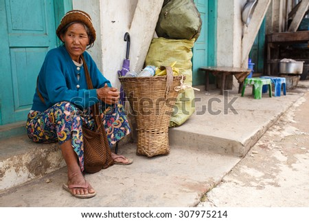 CHIN STATE, MYANMAR - JUNE 18 2015: Older lady sitting on street in the recently opened Chin State Mountainous Region, Myanmar (Burma) - stock photo