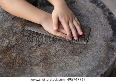 china little girl put both hands on rusty traditional kitchen knife