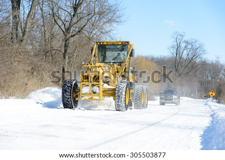 CHINA, MI, USA / FEBRUARY 18, 2014: After a snow fall in China, MI a St Clair County Road Commission road grader clears the road on February 18, 2014.