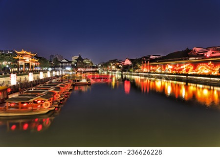 China Nanjing city historic area around confucius temple at sunset with view at city wall with fire breathing dragon ornament, ancient gates and pagodas illuminated and reflecting in still waters  - stock photo
