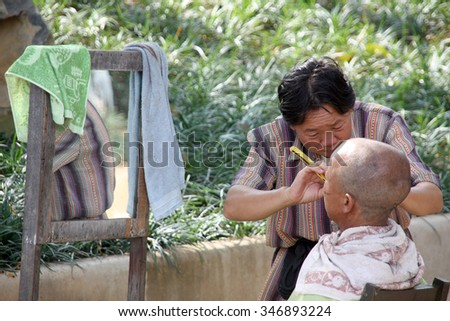 CHINA - NOVEMBER 29.2010: Street woman barber is shaving a man customer in the street stand to earn her day wage on Dec. 01.2011 Yunnan, China - stock photo