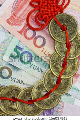 China's money and traditional feng shui coins on red cord - stock photo
