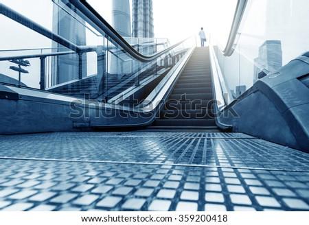 China Shanghai Lujiazui financial district, escalators and walking man. - stock photo