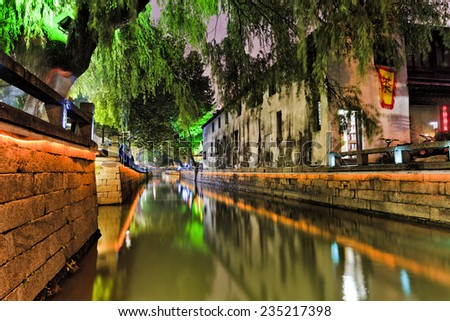 China Suzhou historic town center at sunset still water of canal reflecting ancient houses lights and chinese architecture - stock photo