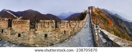 China The Great Wall panoramic view on top of mountains brick wall segment in autumn with yellow trees - stock photo