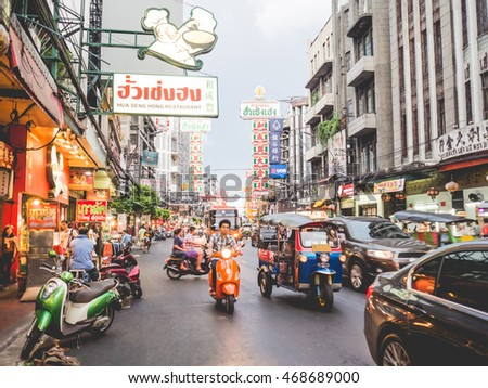 CHINATOWN, BANGKOK, THAILAND - JULY 20, 2016: Cars shops and people on Yaowarat road, the main street of China town.