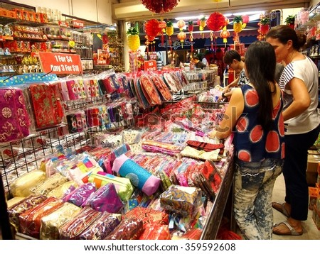 CHINATOWN, SINGAPORE - DECEMBER 29, 2015: Tourists choose from a variety of souvenir products at a store or shop in Chinatown, Singapore.