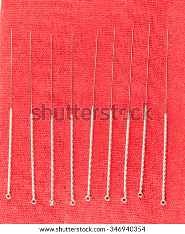 Chinese acupuncture needle on red cloth - stock photo