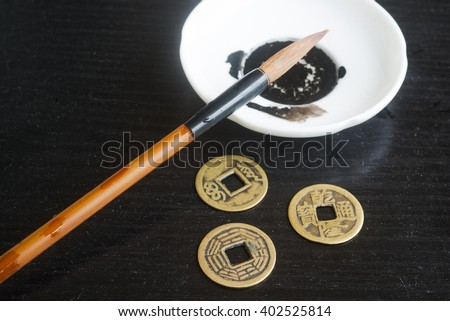 Chinese ancient coins for IChing hexagram and brush for calligraphy. Symbols of I Ching sings ancient coins. Yijing hexagram. - stock photo
