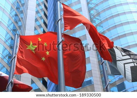 chinese and hong kong flags blow in the wind with glass building background - stock photo