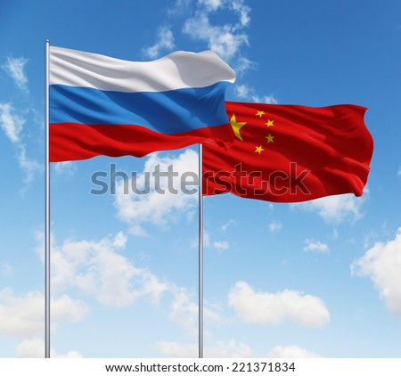 Chinese and Russian flags on a blue sky background. - stock photo