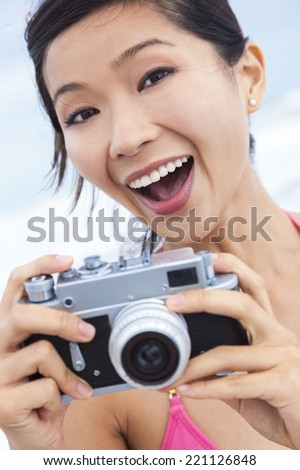 Chinese Asian girl young woman laughing taking vacation photograph in a bikini at the beach using a digital camera - stock photo