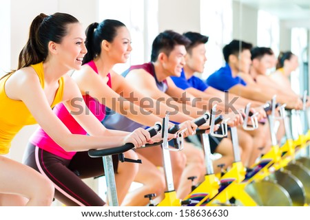 Chinese Asian sport group of men and women in fitness club or gym exercising on bikes   - stock photo