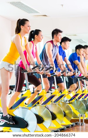 Chinese Asian sport group of men and women in fitness club or gym exercising on spinning bikes  - stock photo