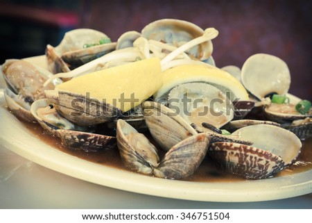 Chinese baby clams sauteed in sweet and spicy black bean sauce with lemon wedge