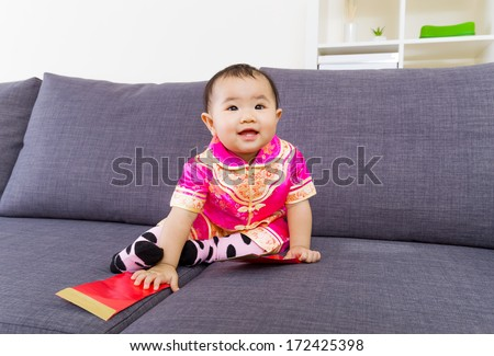 Chinese baby touching red pocket  - stock photo