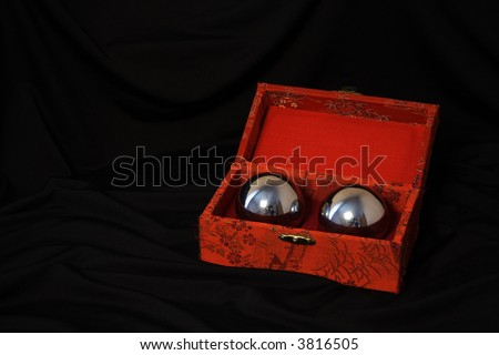 Chinese balls for massage, inside the red box against black background - stock photo
