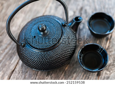 Chinese black tea pot on a wooden background - stock photo