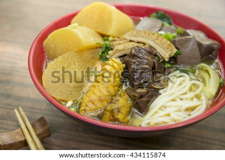 Chinese bowl of noodle with squid, dried pig blood and radish on the table - stock photo