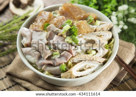 Chinese bowl of vermicelli noodle with pig's guts and herbs on the table - stock photo