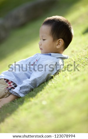 chinese boy lying on the grass with peace