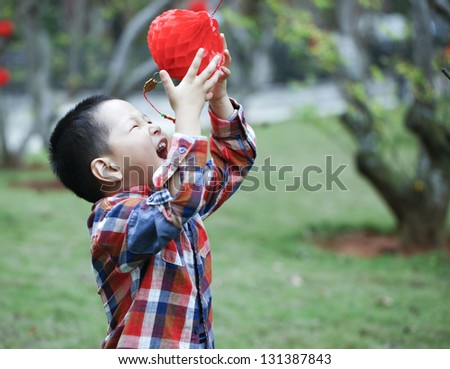 Chinese boy playing red lantern in Chinese lunar new year