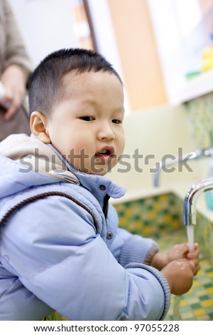 Chinese boy washing the hands beside the tank - stock photo