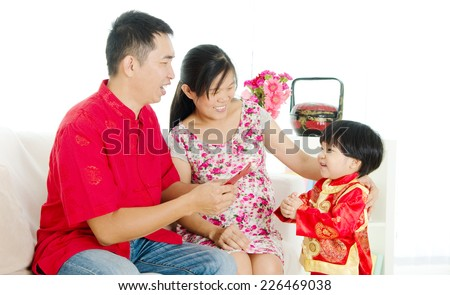 Chinese boy wishing his parent a happy chinese new year - stock photo