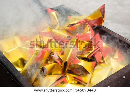 Chinese burning the offering in traditional cremation. - stock photo