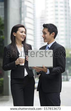 Chinese business Man and woman working together on a laptop outdoors in modern city.