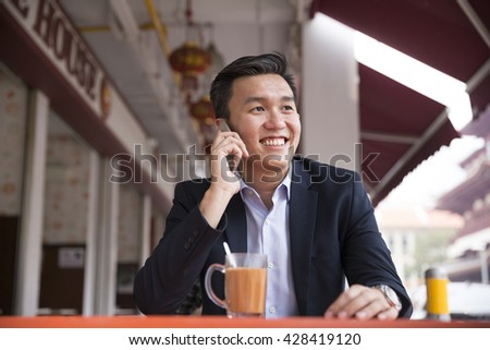 Chinese business man drinking a cup of coffee while sitting with his phone in an Asian food court.
