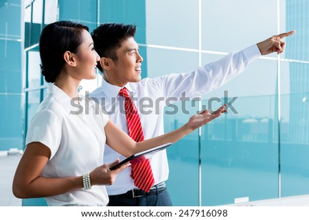Chinese business man explaining his vision or idea to colleague - stock photo