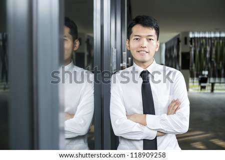 Chinese business man leaning on a window. - stock photo