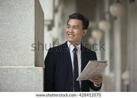 Chinese Business man Outside Office reading a newspaper.