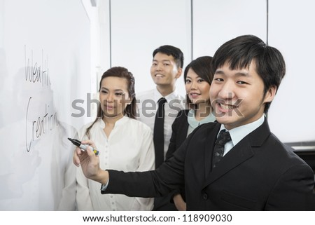 Chinese business man writing on a whiteboard with his team around him. - stock photo