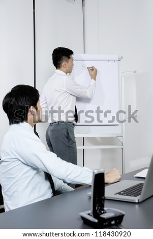 Chinese Business men discussing ideas and writing them on whiteboard. - stock photo