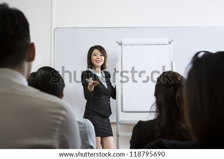 Chinese Business woman giving presentation and interacting with her audience. - stock photo