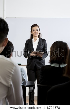 Chinese Business woman giving presentation with a Digital Tablet