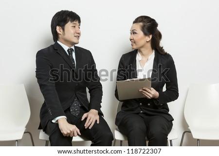 Chinese business woman interviewing an uncomfortable looking male applicant.