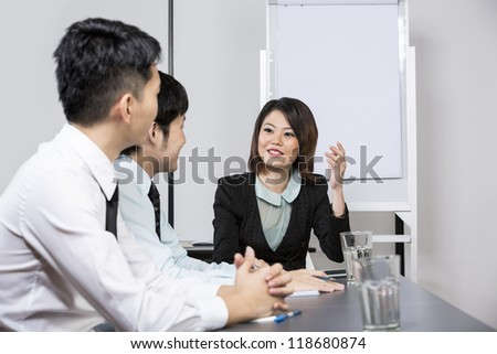 Chinese Business woman leading a meeting in the office. - stock photo