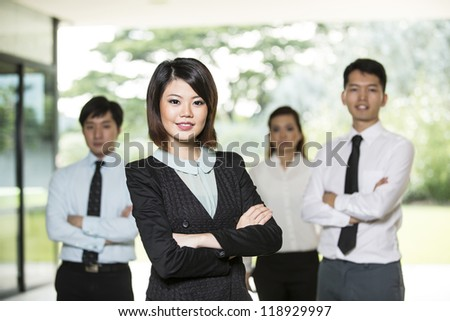 Chinese Business woman standing with her colleagues in the background.