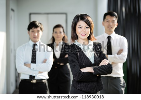 Chinese Business woman standing with her colleagues in the background. - stock photo