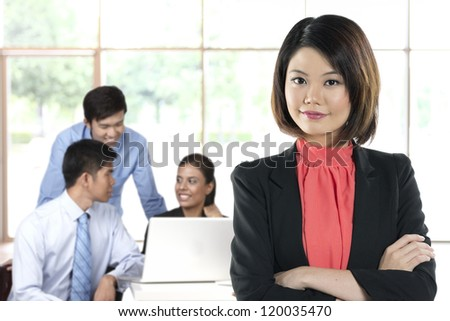Chinese Business woman with colleagues in the background out of focus