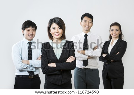 Chinese business woman with her team out of focus behind her. - stock photo