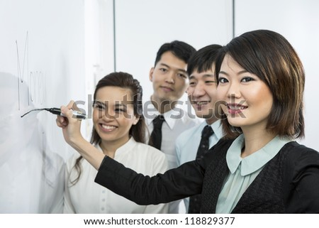 Chinese business woman writing 'Money' on a whiteboard with her team around her.