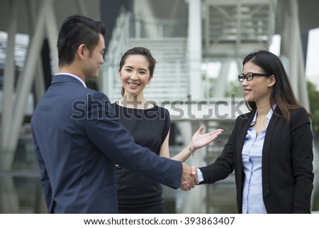 Chinese Businessman and businesswoman shaking hands outside the office.
