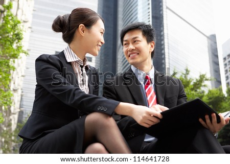 Chinese Businessman And Businesswoman Talking Outside Office - stock photo