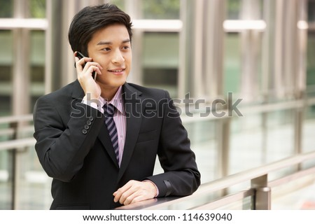 Chinese Businessman Outside Office On Mobile Phone - stock photo