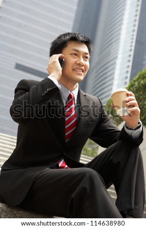 Chinese Businessman Talking On Mobile Phone With Takeaway Coffee - stock photo