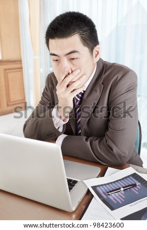 Chinese businessman working in office - stock photo